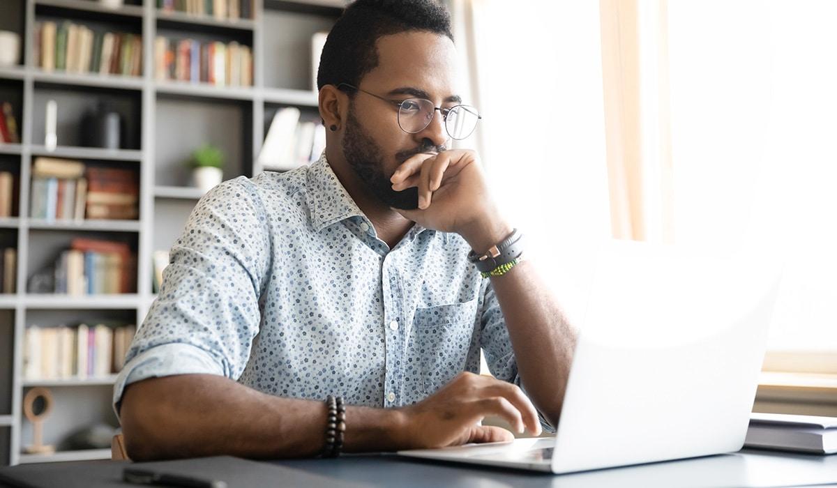 Man pondering while looking at his laptop
